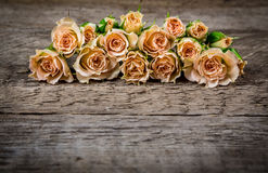Bouquet of little beige roses on wooden rogue table Royalty Free Stock Photography