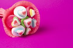 Bouquet of marmalade and sweets in pink packaging on a pink background royalty free stock image