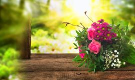 Bouquet for mothers day. Colorful bouquet for mothers day on old rustic wooden table in a sunny garden scenery stock photography