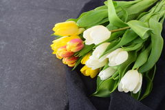 Bouquet of multicolored tulips on a grey cloth. Spring flowers. Romance Royalty Free Stock Photography