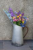Bouquet of multicolored wildflowers in an old metal jug stock photography