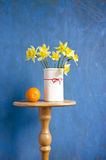 Bouquet narcissus in vase and orange fruit Stock Photo