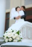 Bouquet and newly married couple kissing Royalty Free Stock Images