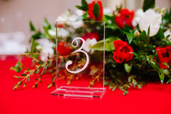 Bouquet and number on guest table on wedding ceremony stock photography