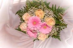 Bouquet nuptiale avec des anneaux sur des roses de pêche et des gerberas roses Images libres de droits
