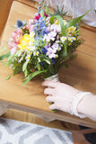 Bouquet nuptiale avec la main de la jeune mariée Image stock