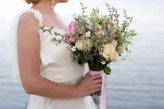 Bouquet nuptiale dans des mains de filles Photographie stock libre de droits