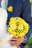 Bouquet nuptiale dans les mains des nouveaux mariés Photographie stock