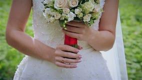 Bouquet nuptiale des fleurs dans des mains de la jeune mariée banque de vidéos