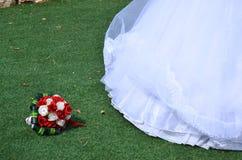 Bouquet nuptiale des roses d'écarlate et blanches avec des feuilles vertes et un bord d'une robe de mariage sur l'herbe Image stock
