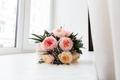 Bouquet nuptiale en pastel des roses roses sur le filon-couche de fenêtre Images stock