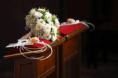 Bouquet nuptiale sur le coussin d'agenouilloir dans l'église Photos stock