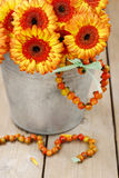 Bouquet of orange gerbera daisies in silver bucket on wooden tab Stock Images