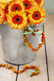 Bouquet of orange gerbera daisies in silver bucket on wooden tab Stock Photos