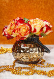 Bouquet of orange and red roses in golden vase Royalty Free Stock Photo