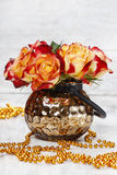 Bouquet of orange and red roses in golden vase Royalty Free Stock Image