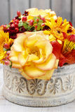 Bouquet of orange roses and autumn plants in vintage ceramic vas Royalty Free Stock Photo