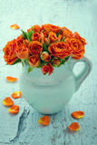 Bouquet of orange roses in a blue vase Stock Photography