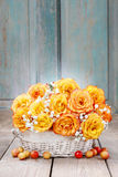 Bouquet of orange roses in a white wicker basket Royalty Free Stock Photos