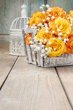 Bouquet of orange roses in a white wicker basket and vintage bir Royalty Free Stock Photo