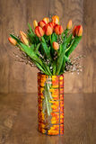 Bouquet of orange tulips in glass colorful vase Stock Photo