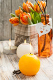 Bouquet of orange tulips, lit candles. And Easter decoration. Springtime composition Stock Images