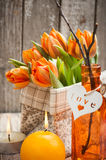 Bouquet of orange tulips, lit candles. And Easter decoration. Springtime composition Royalty Free Stock Photo