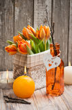 Bouquet of orange tulips, lit candles. And Easter decoration. Springtime composition Stock Photos