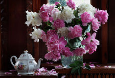 Bouquet of peonies and brewing teapot. Still-life with white both pink peonies and a beautiful teapot stock photo