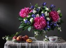 Bouquet of peonies, irises and Jasmine in the jar and the peache. Bouquet of peonies, irises and Jasmine in the jar and peaches on a table with lace tablecloth Stock Image
