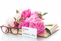 Bouquet of peonies  on old book with glasses Royalty Free Stock Photos