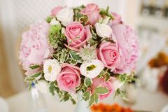 Bouquet of peonies and roses in a vase on a served table stock photos