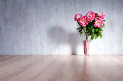 Bouquet of peonies in a vase against a blue wall. Royalty Free Stock Image