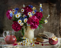 Bouquet with pi-mesons, corn-flowers and camomiles. Still life with pi-mesons, corn-flowers and camomiles in a vase, alongside taken a bite apple Royalty Free Stock Photo