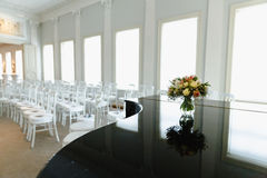 Bouquet on a piano white chairs in a row. Bouquet on a piano with white chairs on background Royalty Free Stock Photography