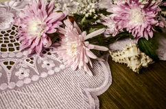 Bouquet of pink asters with sea shell on lacy napkin Royalty Free Stock Photos