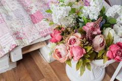 Bouquet of pink flowers in a vase near the bed Stock Photo