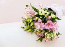 Bouquet of pink and green flowers. On white sofa Royalty Free Stock Photo