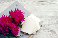 Bouquet of pink peonies, old photo album, old empty photographs Royalty Free Stock Photo