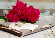 Bouquet of pink peonies, old photo album, old empty photographs and a pocket watch Stock Photos