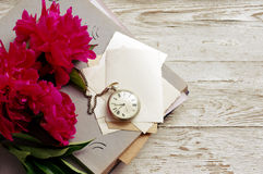Bouquet of pink peonies, old photo album, old empty photographs and a pocket watch Stock Photo