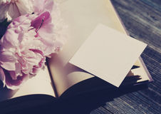 Bouquet of pink peonies on an open book an empty white card for the text Royalty Free Stock Photo
