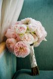 Bouquet of pink peonies propped on a chair Stock Photos