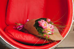 Bouquet of pink peonies. On red-steel chair Royalty Free Stock Photos