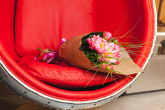 Bouquet of pink peonies. On red-steel chair Stock Image