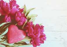 Bouquet of pink peonies and red wooden heart on the old painted wooden background Stock Photography