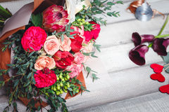 Bouquet of pink and red roses lies on a wooden table, spase for text Royalty Free Stock Image
