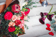 Bouquet of pink and red roses lies on a wooden table, spase for text Stock Images