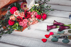 Bouquet of pink and red roses lies on a wooden table, spase for text Royalty Free Stock Photo