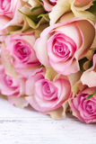 Bouquet of pink roses with blue ribbon for present on a vintage wooden background, copy space Royalty Free Stock Photography